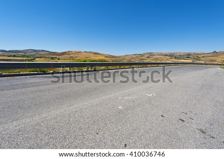 Asphalt Road between Stubble Fields of Sicily