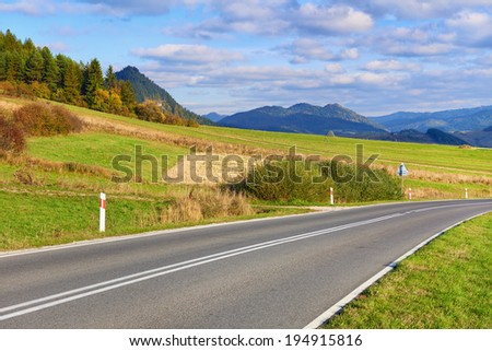 Asphalt Road by The Pieniny Mountains landscape, Carpathians. Daylight scenery with way in the environment of trees, meadows, mountains and clouds on blue sky. - stock photo