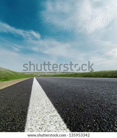 asphalt road closeup to cloudy horizon - stock photo
