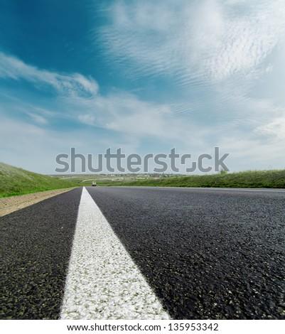 asphalt road closeup to cloudy horizon - stock photo