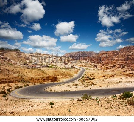 Asphalt road in a desert with blue cloudy sky on the background - stock photo