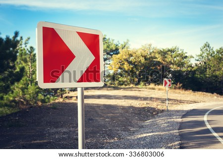 Asphalt road in autumn forest at sunrise and road sign. Crimean mountains.