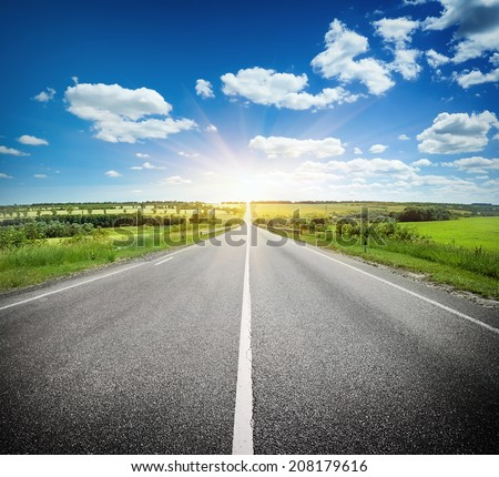 Asphalt road in field under blue cloudy sky