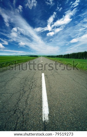 asphalt road in field under blue sky - stock photo