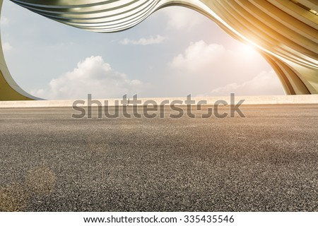 Asphalt road in front of the modern building - stock photo