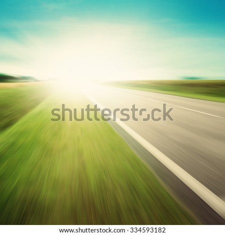 Asphalt road in motion blur and sunlight. - stock photo