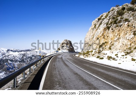asphalt road in mountain peak with snowfields - stock photo