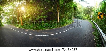 Asphalt road in mountains. Panorama at sunrise light - stock photo