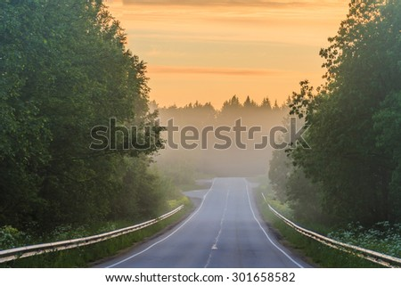 asphalt road in Russia. Empty asphalt road at sunset. The asphalted road with protections at sunrise. Foggy morning on the road - stock photo