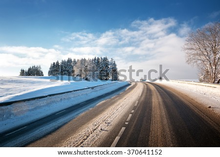 Asphalt road in snowy winter on beautiful sunny day - stock photo