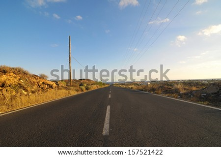 Asphalt Road in the Desert on a Colored Sunset - stock photo