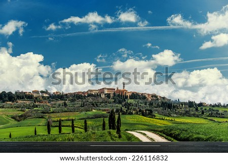 asphalt road in the fields of Tuscany, Italy - stock photo
