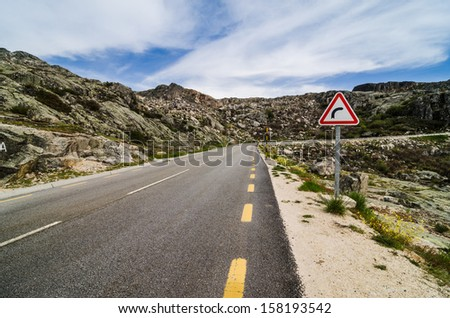 Asphalt road in the mountains and blue sky with clouds. - stock photo