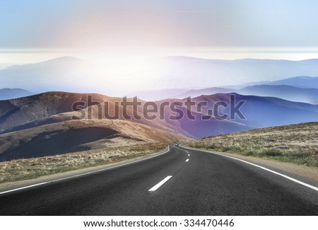 Asphalt road in the mountains with soft sky on the background. - stock photo