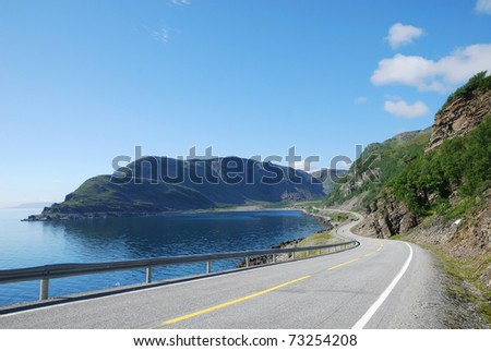 Asphalt road is meandering between blue fjord and moss mountains.  Mageroya is an island in Finnmark county in the extreme north of Norway. - stock photo