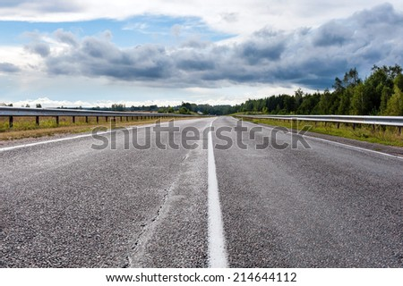 asphalt road low point view in cloudy summer day - stock photo
