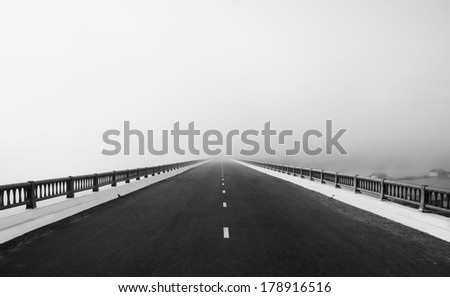 Asphalt road on big bridge cross the lake in fog at morning, the way like arrow, direction to white future, atmosphere full misty   - stock photo