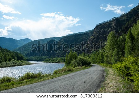 Asphalt road on the background of the Sayan mountains on a summer day. Russia, Siberia. Highway M-54. - stock photo