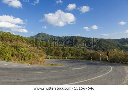 Asphalt road sharp curve on the mountain - stock photo