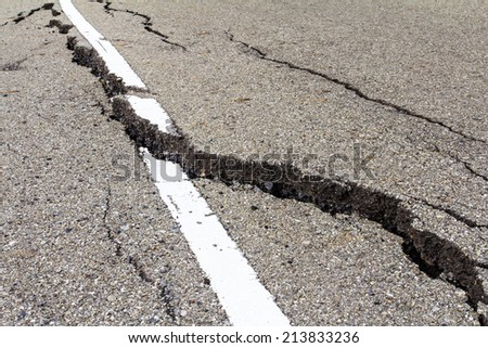 Asphalt road surface crack is dangerous because of corruption. - stock photo