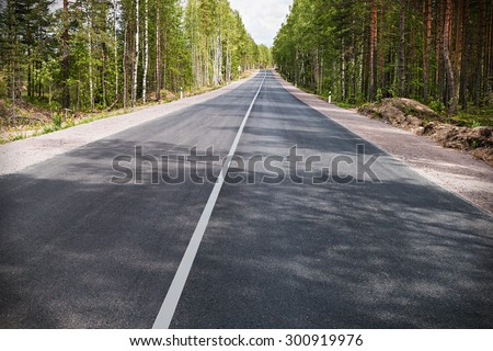 asphalt road through the forest. Focus on the end of the highway - stock photo