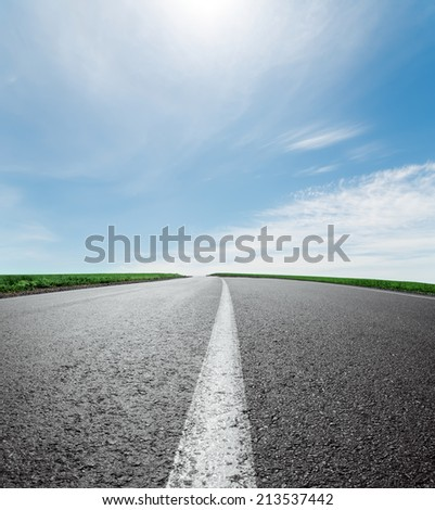 asphalt road to horizon under sky with clouds and sun - stock photo