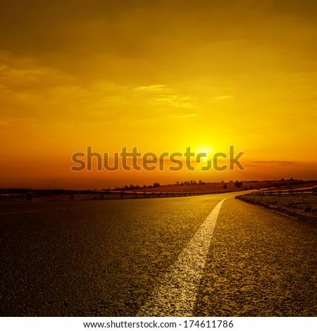 asphalt road to orange horizon in sunset - stock photo