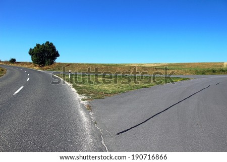 asphalt road triangle crossroad in nature - stock photo