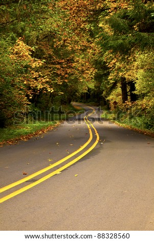 Asphalt road winding through the Oregon countryside that is displaying its seasonal colors. - stock photo