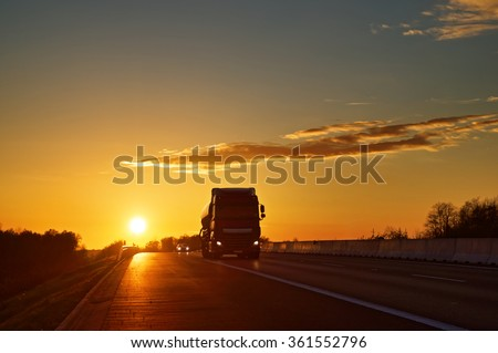Asphalt road with oncoming truck in a rural landscape at sunset. - stock photo