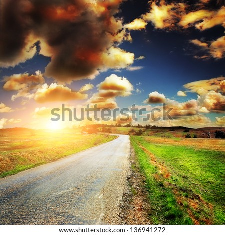 asphalt road with the green fields - stock photo