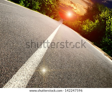 asphalt road with the green forest - stock photo