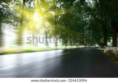 asphalt road with tree lawns under sunshine - stock photo