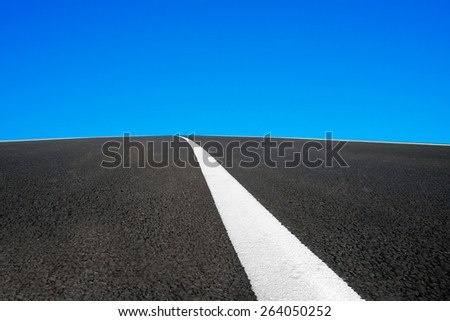 Asphalt road with white line and blue sky background - stock photo