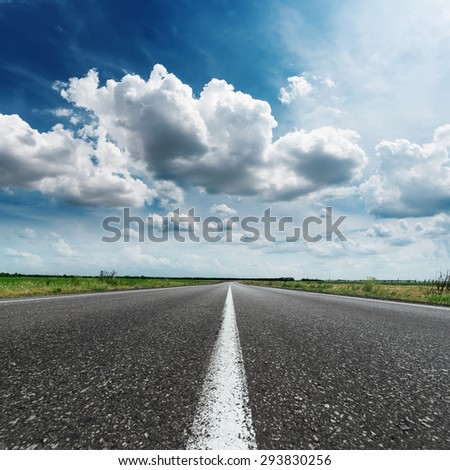 asphalt road with white line on center under dramatic sky and clouds