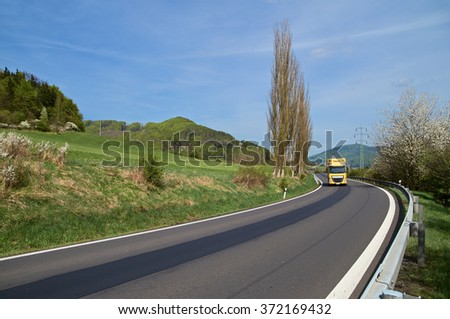 Asphalt road with yellow truck ride between forested mountains in the spring. Flowering trees. Sunny spring day with blue skies.