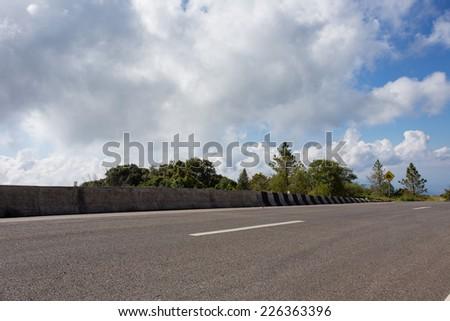 asphalt roadway with cloud blue sky background - stock photo