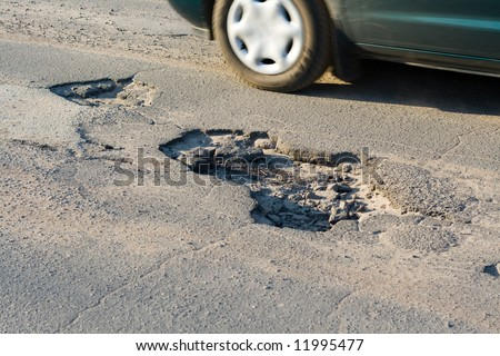 Asphalt`s holes on roadbed. Car in a motion. - stock photo