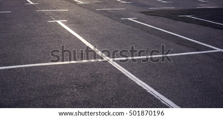 Asphalt surface of the empty parking with white road marking lines and wheel tracks, Empty parking place with white marking lines on asphalt, Acres of empty parking spaces