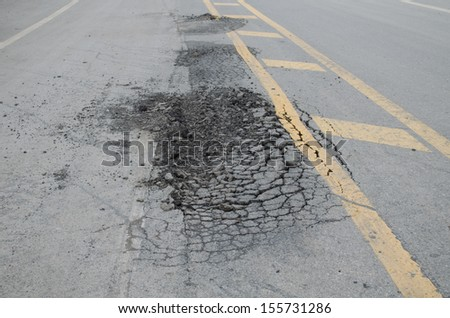 Asphalt surface, on of the road were demolished due to poor construction. - stock photo
