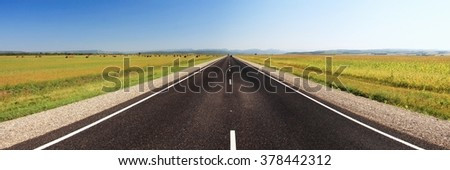 Asphalt symmetric road through the green field on blue sky in summer day panorama - stock photo
