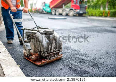 asphalt worker at road repairing and construction site with manual compactor plate - stock photo