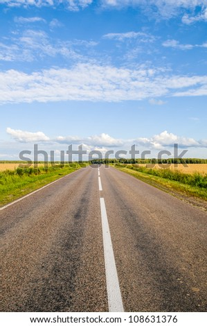 asphalted road goes into the distance through the fields - stock photo