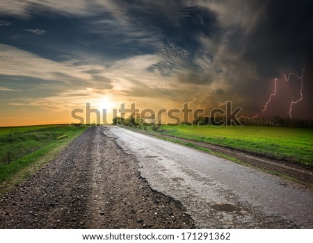 Asphalted road in poor condition at sunset and stormy sky - stock photo