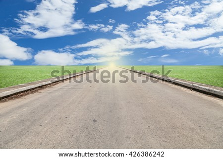 asphalted road with green grass blue sky background