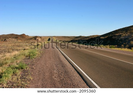 asphaltic road in a prairie by a hot canicular day - stock photo