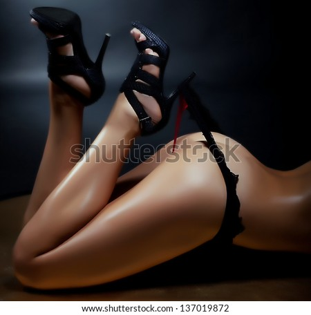 Aspiration. Sexy Woman Pulling her Black Thong Panties with Heel. Shiny Golden Body - stock photo