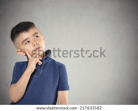 Aspirations. Closeup portrait, headshot thinking, daydreaming child boy finger on face, looking up, isolated grey wall background. Positive human facial expression, emotions, feeling life perception - stock photo