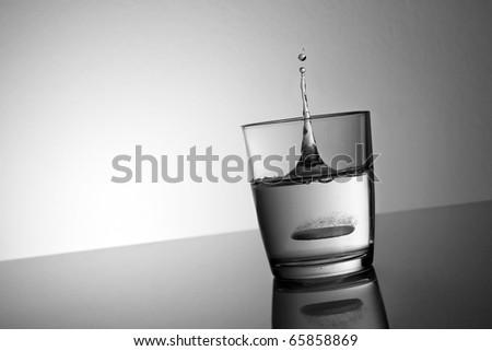 Aspirin drop into water glass - stock photo
