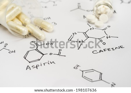 Aspirin in capsules and caffeine in tablets on paper with their chemical formula - stock photo